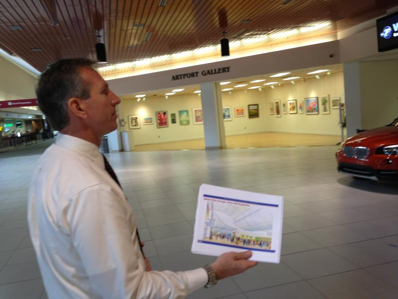 Interim Airport Director Jay Townsend holds an architect's rendering of upgrades to the airport lobby (background).