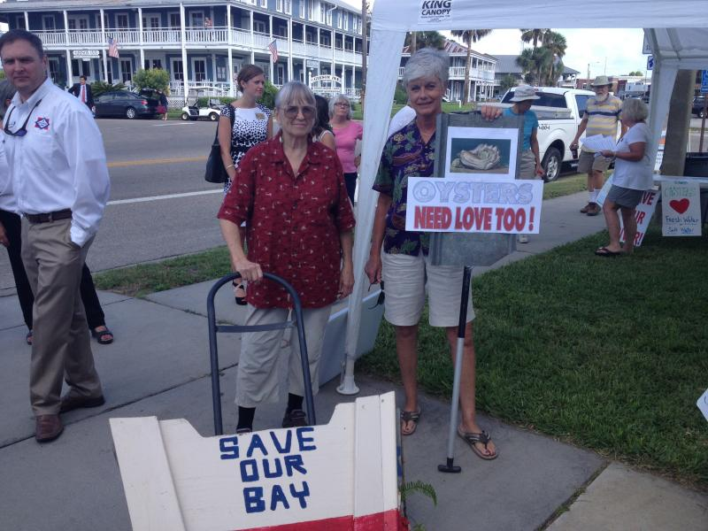 Two Apalachicola residents hold handmade signs calling for a solution to the fishery disaster.