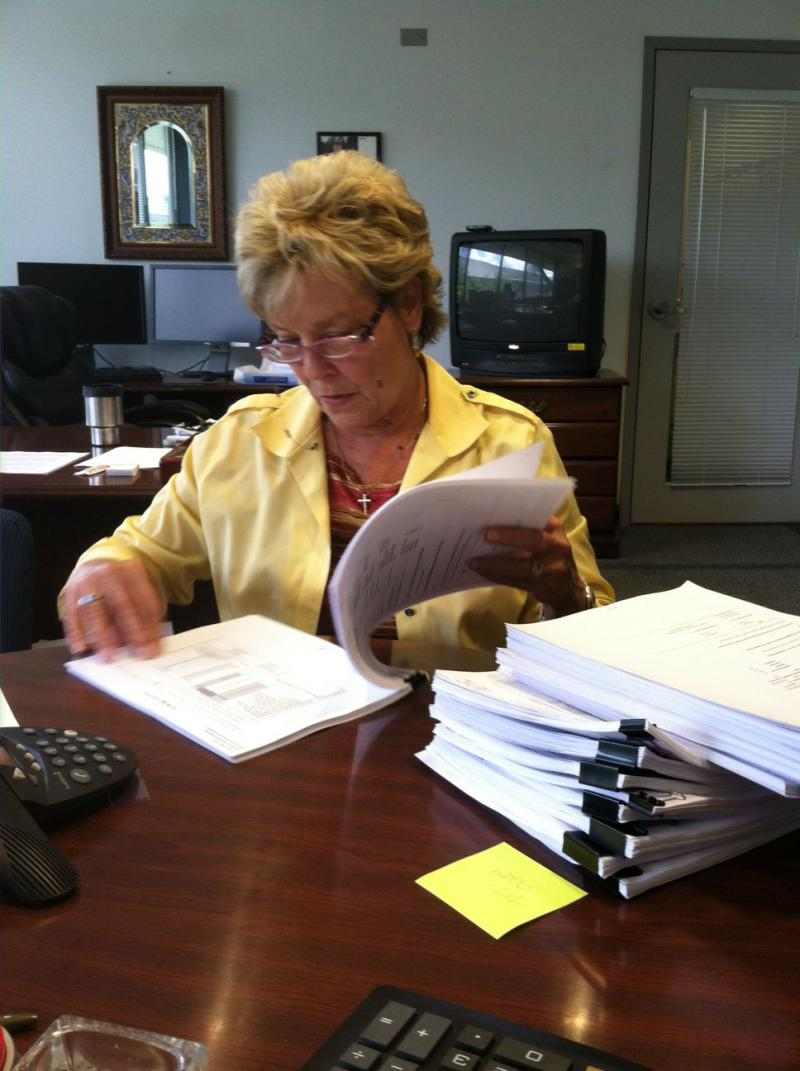 APD Director Barbara Palmer sifts through files of appeals. Each file is a person requesting an increase in their Medicaid funding. Palmer says she reviews them personally.