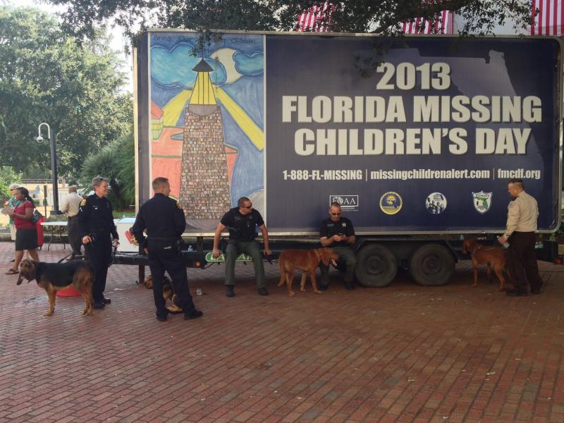 Officers from various agencies stand by a missing child billboard with their blood hound partners.