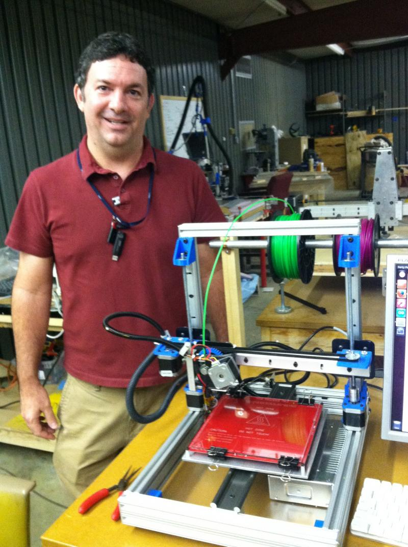 Computer Engineer with Technology Services Group Mark Trombly next to a 3D printer he made. He's the top 3D printing expert at Making Awesome in Tallahassee, community of people who share tools, materials and their talents.