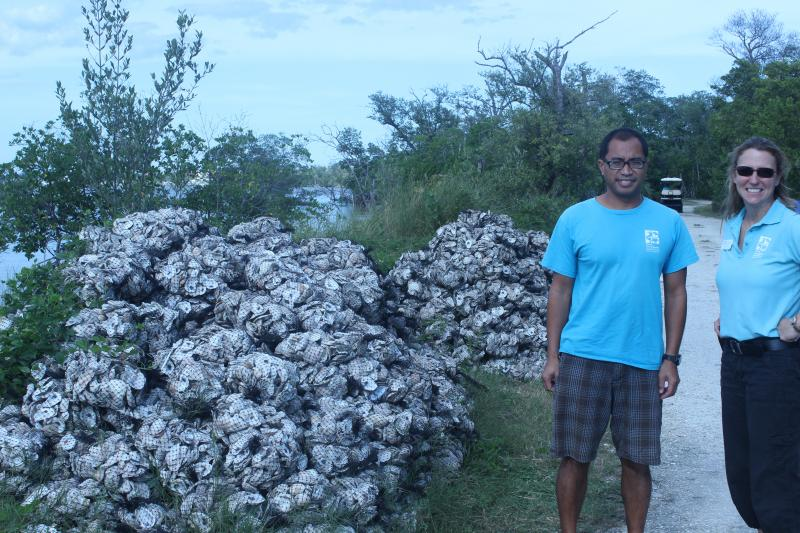 Vincent Encomio and Roberts, along with piles of oyster shells for reef reconstruction