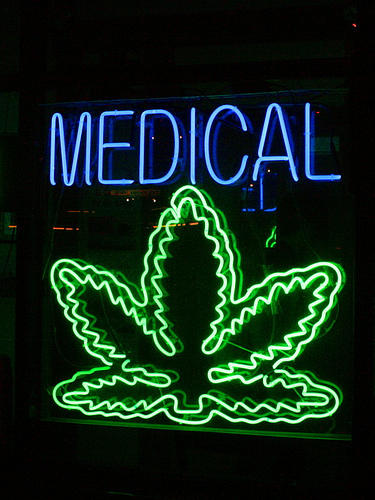 A neon sign reading medical with a marijuana leaf beneath it.