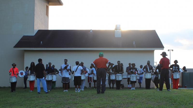 The drumline warms up Thursday evening as band director Sylvester Young looks on.