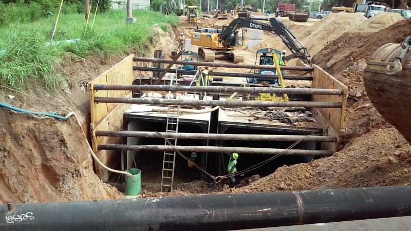 Workers install culverts in the St. Augustine Branch to reduce sendiment pollution.