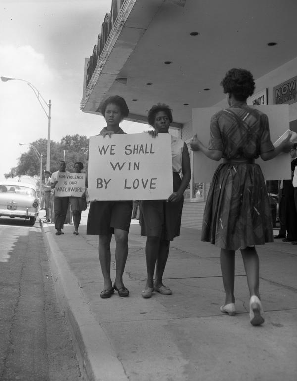 "women holding ""we shall win by love"" sign"