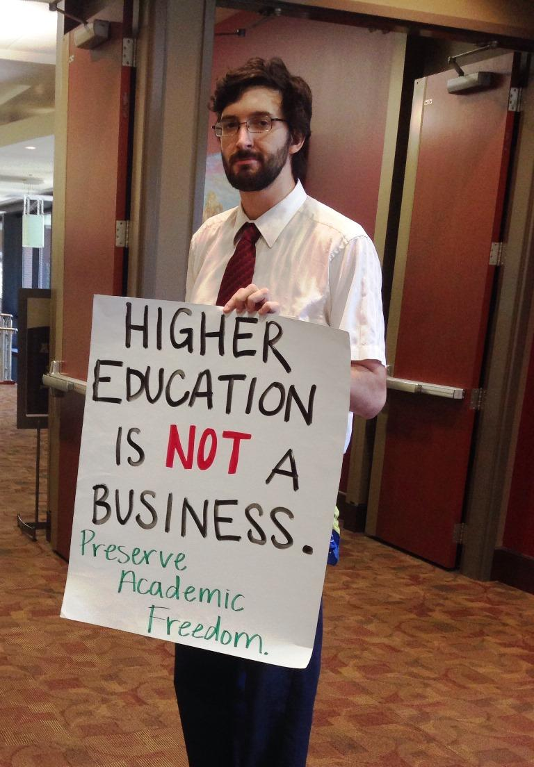 "Man holding ""higher education is not a business"" sign"