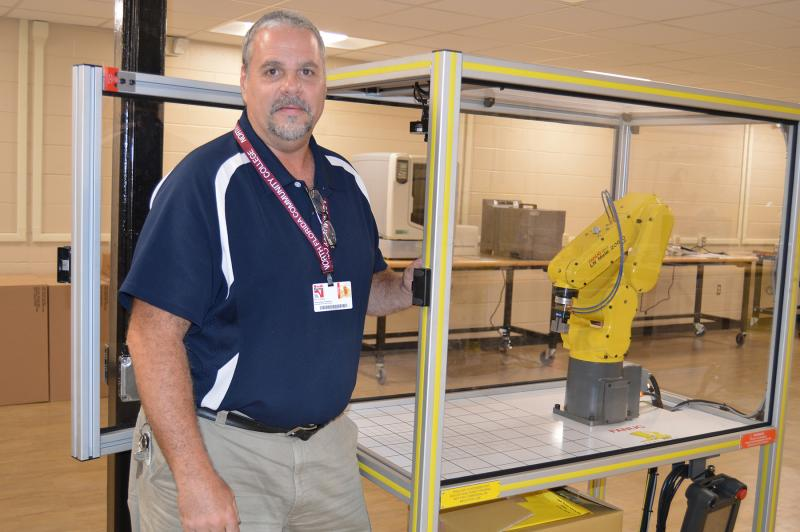 Bill Eustace stands beside NFCC's FANUC robot