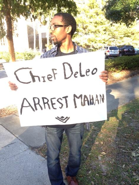 "Marshall holding ""Chief DeLeo Arrest Mahan"" sign"