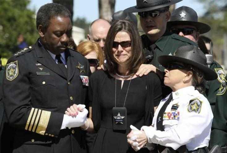 Orange County Sheriff Jerry Demings (left) escorts Deputy Jonathan Scott Pine's widow, Bridget, into First Baptist Church of Orlando, Saturday, Feb. 15, 2014, for the funeral service.