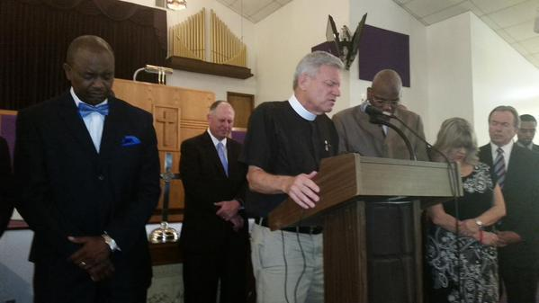 Tallahassee Pastor Brant Copeland (center, podium) in prayer at Bethel Baptist Chruch.