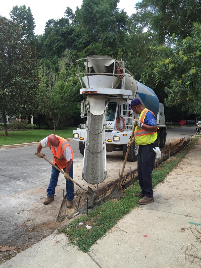 2 men pouring concrete into a new curb mold