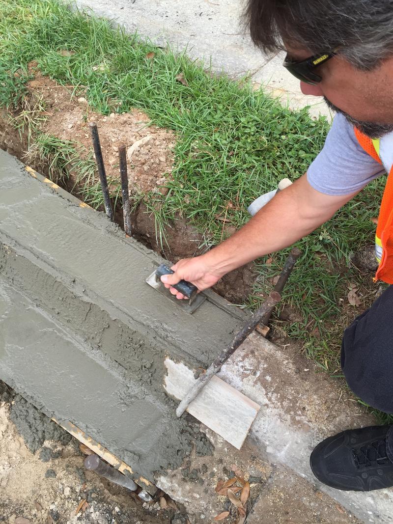 man smooths concrete