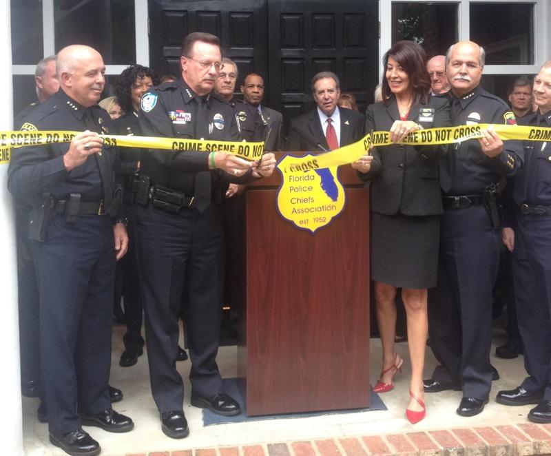 Winter Park Police Chief Brett Railey is cutting the ribbon to unveil the Florida Police Chiefs Association's new headquarters, as other members look on.