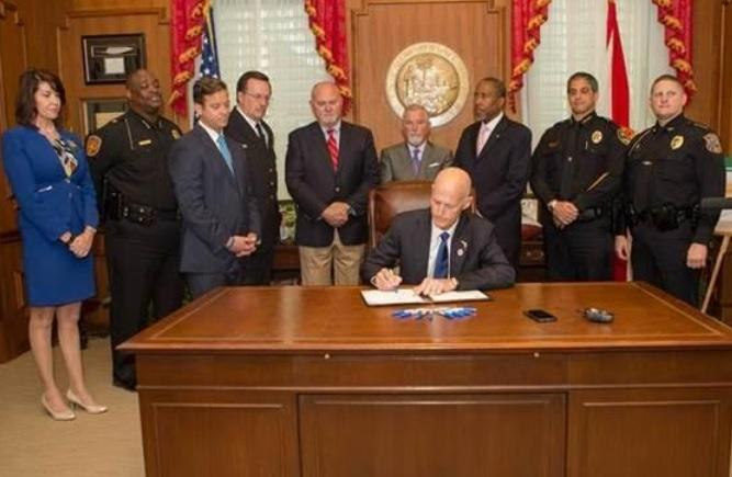 Surrounded by stakeholders, Gov. Rick Scott is signing a bill making it illegal to discharge a firearm in certain residential neighborhoods into law Wednesday.