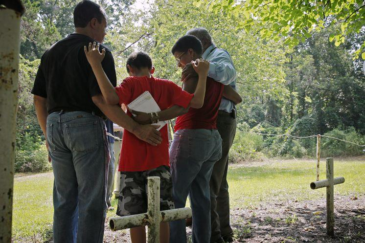 The Due Family, including patriarch John Due (far right) embrace during a memorial ceremony at the Boot Hill cemetery at the Dozier School for Boys in Marianna back in 2013. John Due's wife's uncle died at the school in 1937.