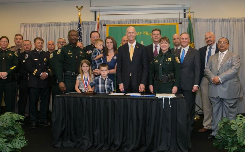 Joined by former Orange County Sheriff's deputy Scott Pine's family as well as other law enforcement and officials, Gov. Scott ceremonially signed Senate Bill 7012 into law Monday, for the second time.