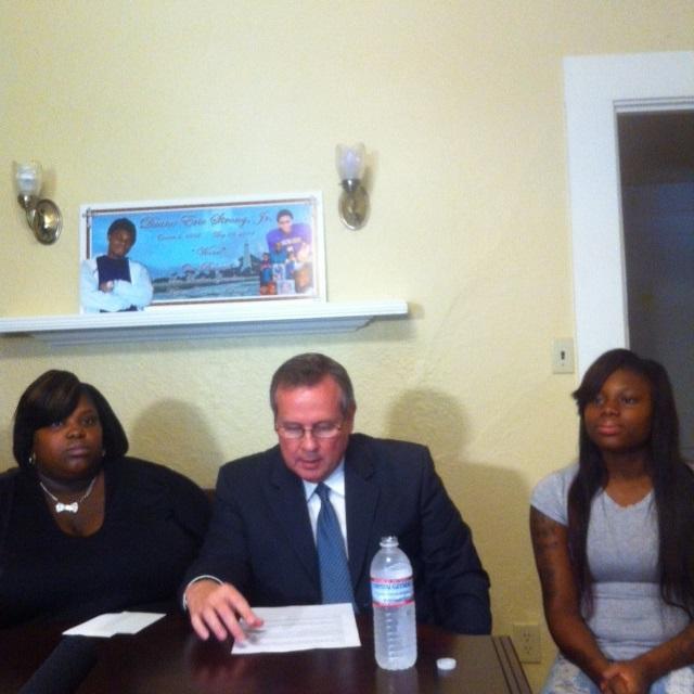 Ayouna McClinton, David Frank, and Gariah Jones sit together at a press conference (2014).