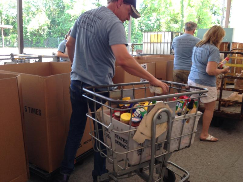 Workers and volunteers help sort and stock a Tallahassee food bank.