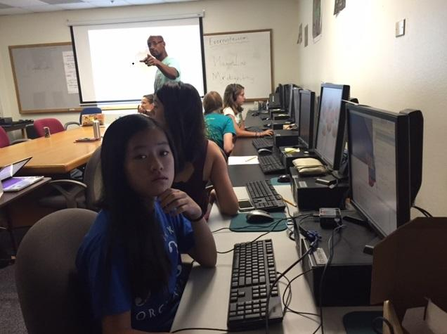 Vincent Hunt (background) leads a group of teenage girls in Creators Camp, a program aimed at helping girls refine their coding skills.