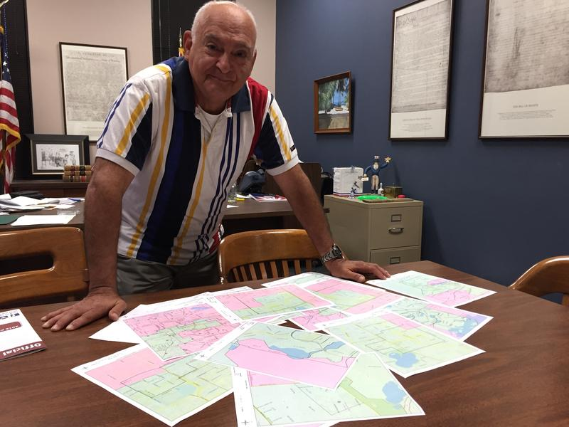 Leon County Supervisor of Elections Ion Sancho standing over blown up images of the county's voting precincts.