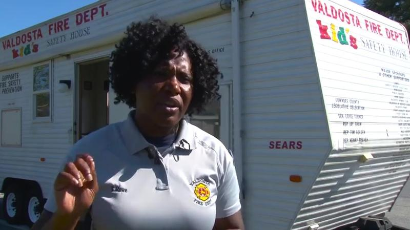 "Valdosta Fire Department Senior Community Educator Tangela Rowe speaking in front of VFD's ""Kid's Safety House."""