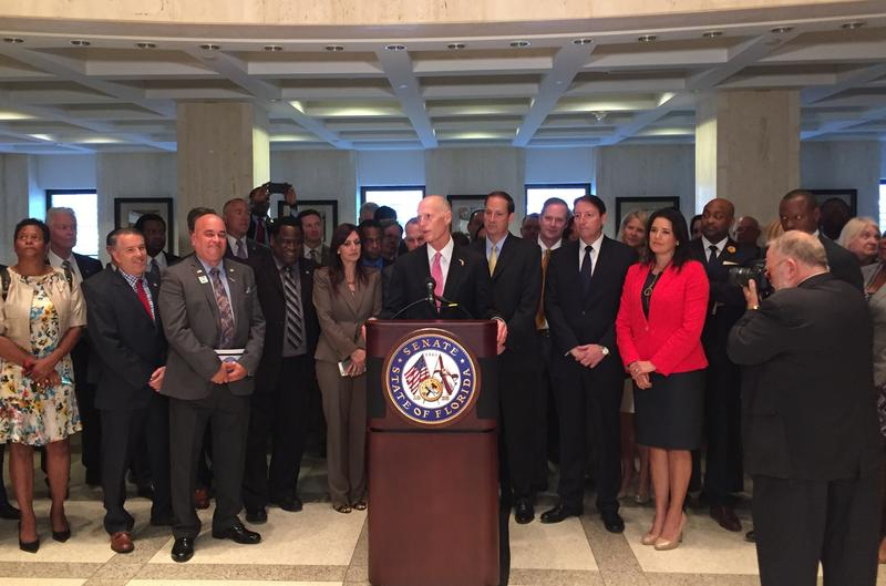 Gov. Scott flanked by lawmakers speaking at the end of last week's special session.