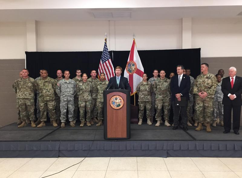 Commissioner Adam Putnam, flanked by state officials and Florida guard members, speaking at an armory in Tallahassee.