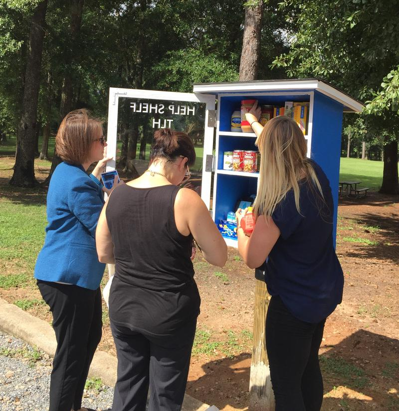 Three women surround a small food pantry