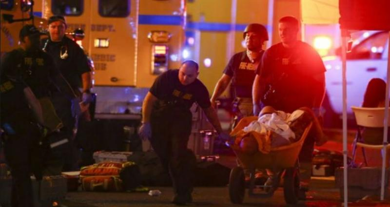 A wounded person is walked in on a wheelbarrow as Las Vegas police respond during an active shooter situation on the Las Vegas Strip Sunday. Multiple victims were being transported to hospitals after Sunday's mass shooting at a music festival.