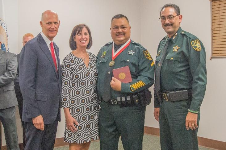 (from right to left) Marion County Sheriff Billy Woods, Deputy Jimmy Long, Long's wife, and Gov. Rick Scott, following SRO Long's Medal Of Heroism presentation.