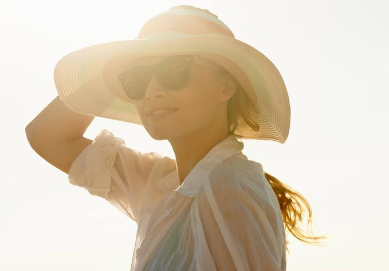 A lady wearing a hat while the sun beams down on her
