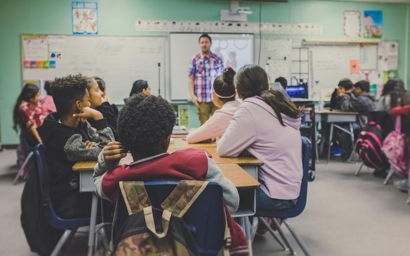 Students listen to a teacher in a classroom