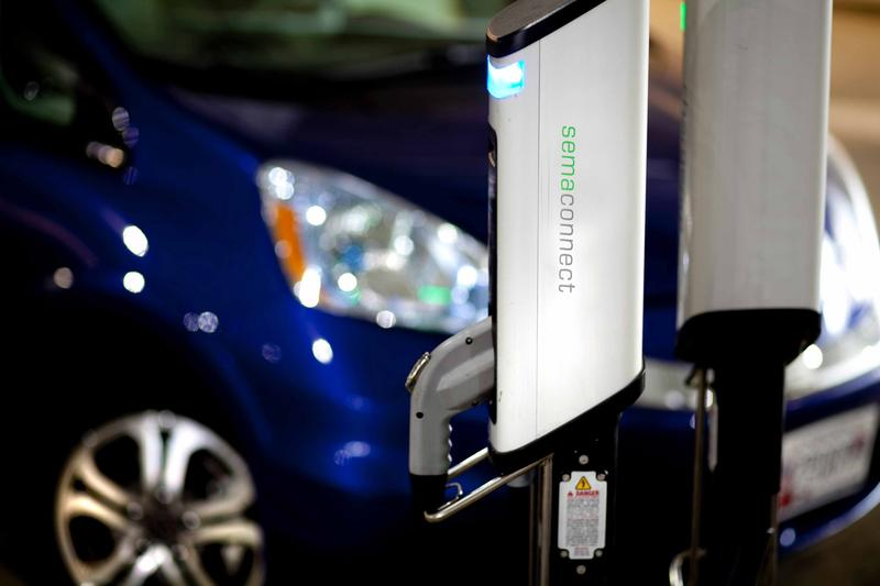 A blue car uses a SemaConnect charging station.