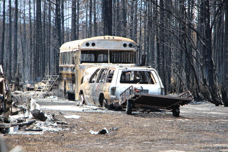 A school bus and car are burned out and covered with ash from a wildfire.