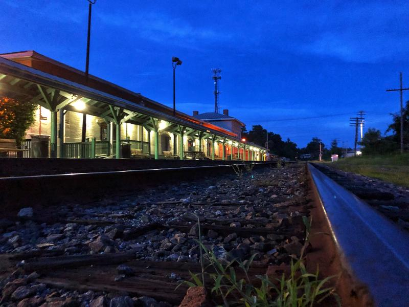 Train tracks pass a lit train station as dusk falls