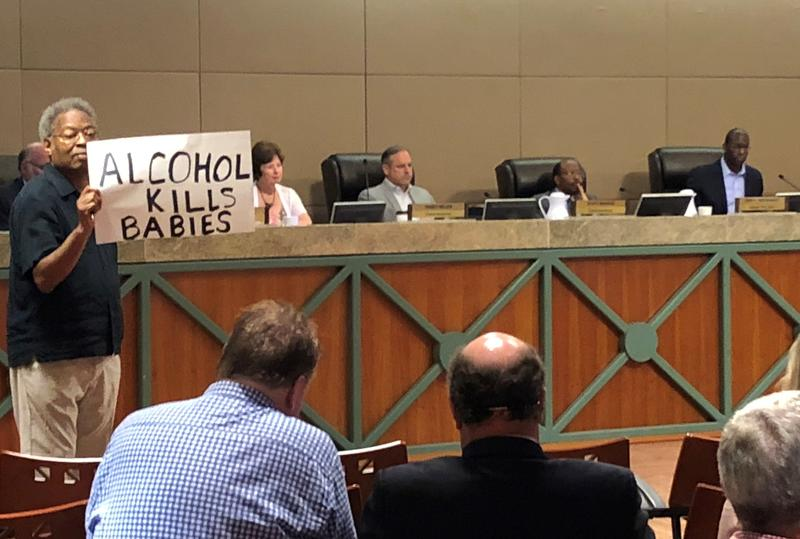Man holds up a sign during the Monday CRA meeting