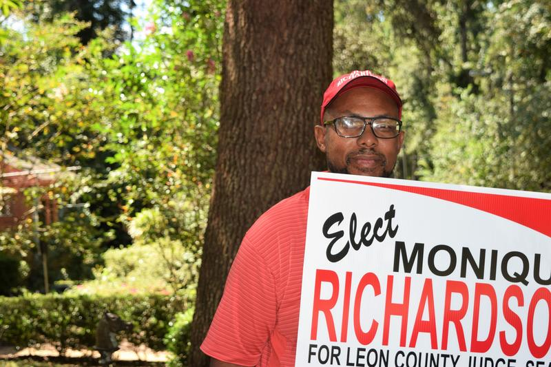 A man in a red polo holds a sign for Monique Richardson