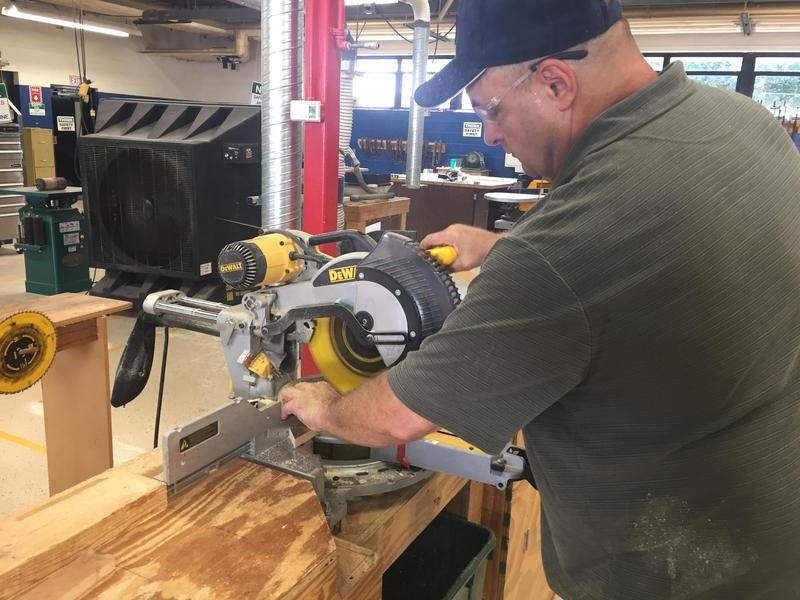 A man operates a circular saw in a wood shop