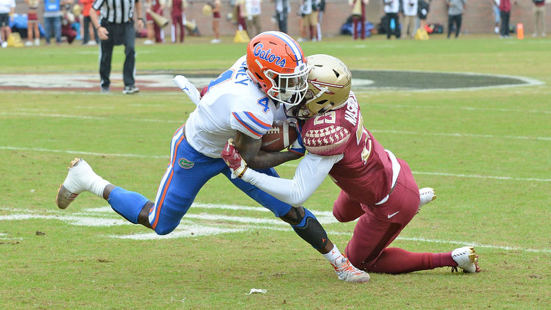 UF's Hamsah Nasirildeen tackles FSU's Kadarius Toney during the FSU-UF game (2018).