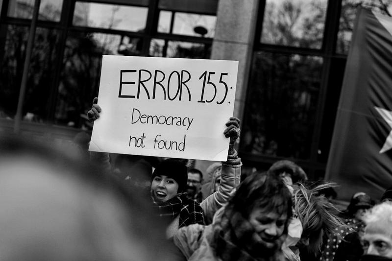 "A person holds a white Error 155 sign reading ""Error, Democracy not found."""