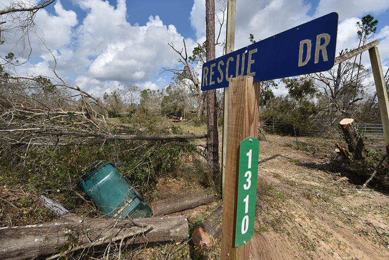 rescue drive street sign in front of hurricane debris