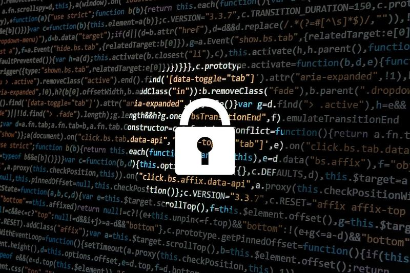 Image of a lock in front of a computer screen with code
