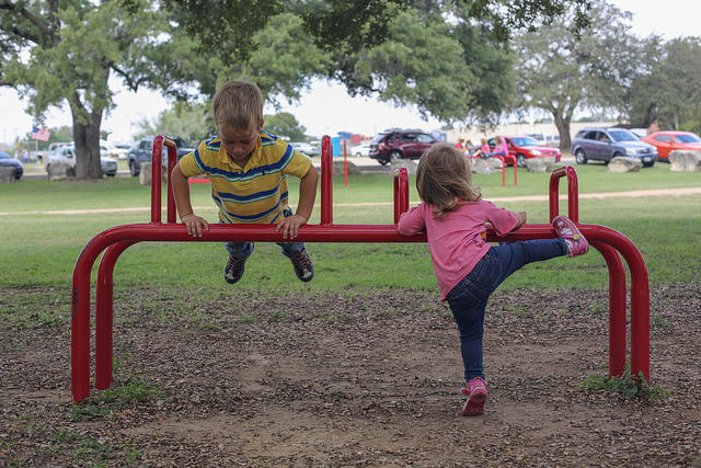 small children climbing on monkey bars