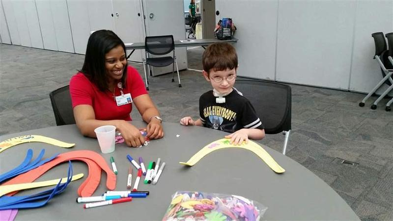 Five-year-old Lakota Lockhart, who has a complex medical condition, works on an art project with a volunteer at St. Joseph's Children's Hospital in Tampa, Florida. A few hospitals in the U.S. have managed to deliver better care to kids like Lockhart for l