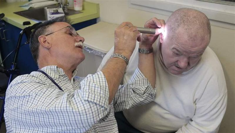 Dr. David Mathis examines the ear of an inmate at the California Medical Facility in Vacaville in 2012. California is one of at least 38 states that authorize the collection of medical fees from inmates.