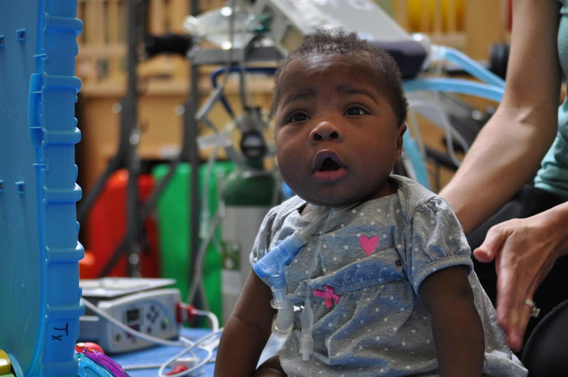Janayla, 1, plays with toys during a physical therapy session at Ranken Jordan.