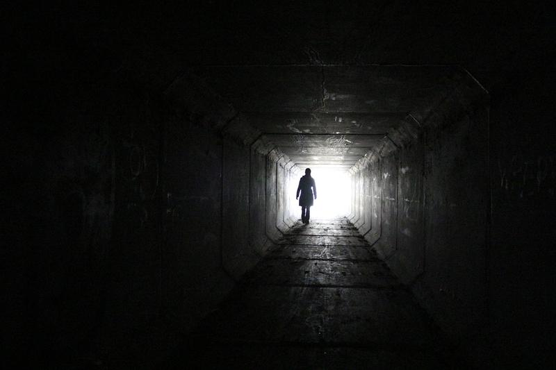 Figure in sillouette at the end of a dark tunnel