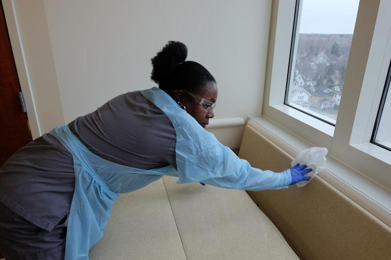 Environmental services worker Jeanna Hibbert scrubs the hospital room to get rid of C-diff bacteria.