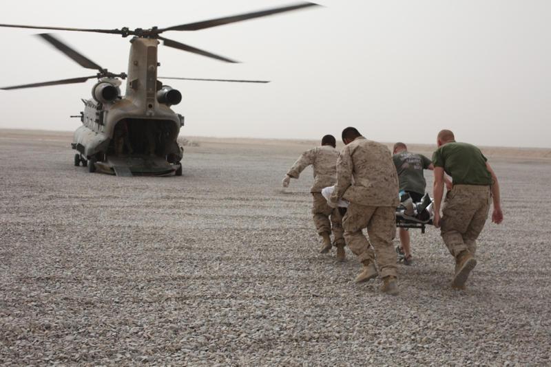 US Marines and Sailors cary a wounded Afghan civilian to a medical transport after an IED explosion.